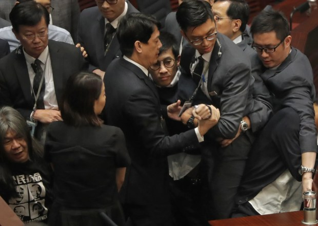 Newly elected Hong Kong lawmaker Sixtus Leung, center with glasses, is blocked by security guards wearing gray suits, as he tries to retake oath at legislature council in Hong Kong, Wednesday, Nov. (AP Photo/Vincent Yu)