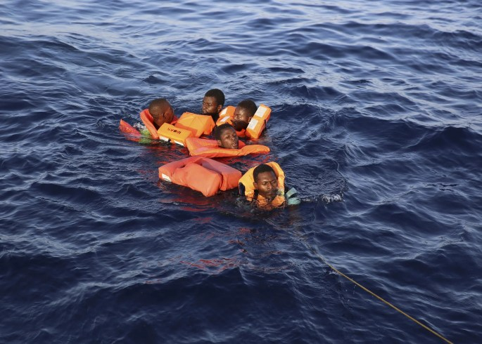 Migrants who fell in the water from a crowded rubber dinghy are rescued by the vessel Responder, run by the Malta-based NGO Migrant Offshore Aid Station (MOAS) and the Italian Red Cross, in the Mediterranean sea, Thursday, Nov.