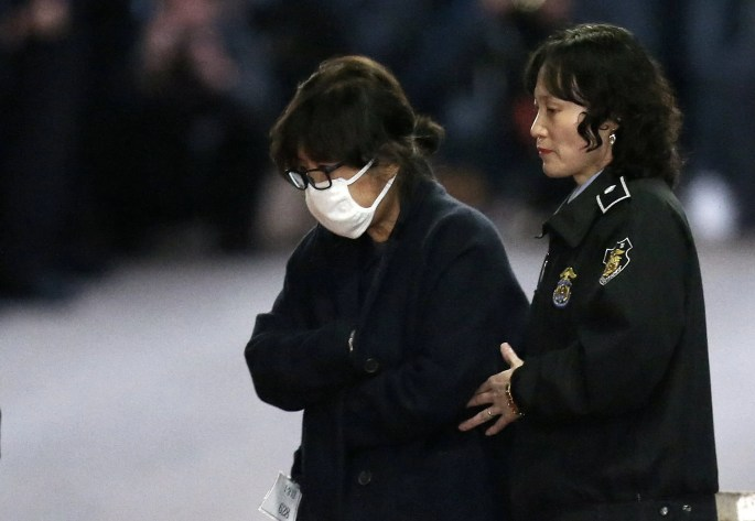 Choi Soon-sil, a longtime friend of South Korean President Park Geun-hye, left, is escorted to get on a bus of Ministry of Justice as she leaves the Seoul Central District Court in Seoul, South Korea, Thursday, Nov.