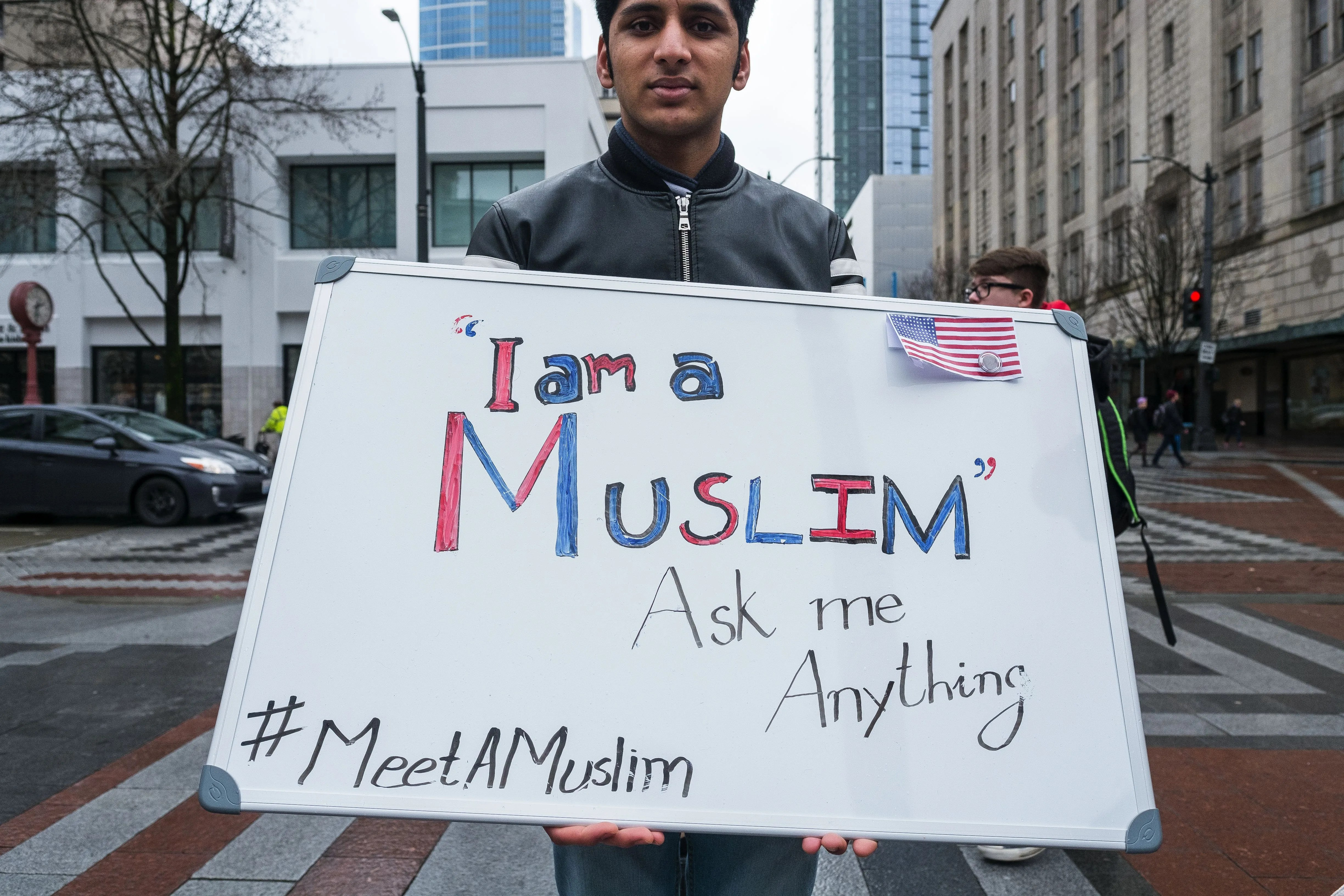 Faiez Ahmad joins two of his friends in Westlake Park. About 30 or 40 people stopped by to speak to them, including people attending a St. Patrick's Day Parade. Young Muslims also fielded questions at Green Lake the University District and Pike Place Market. (Dean Rutz/The Seattle Times)