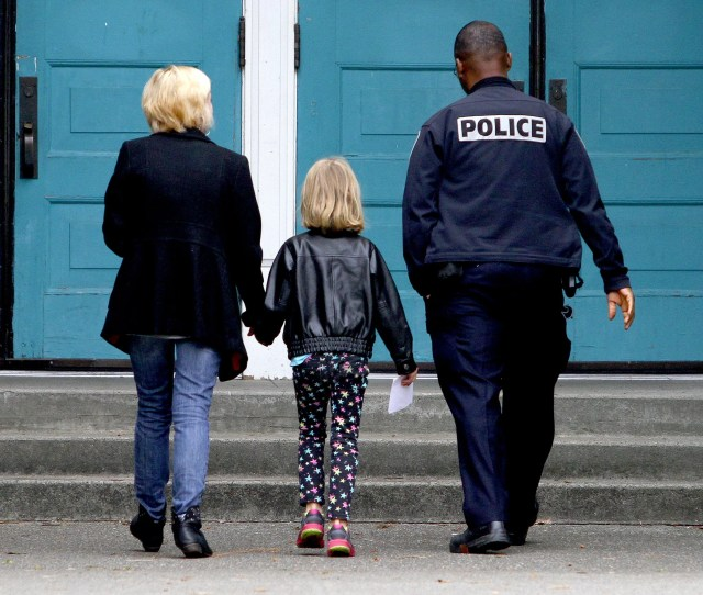 A Seattle Police Officer Escorts A Child And Another Adult Into A Seattle School