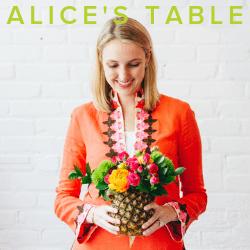 Advertisement photo for Alice's Table. Shows a woman holding a floral bouquet standing in front of a white wall.