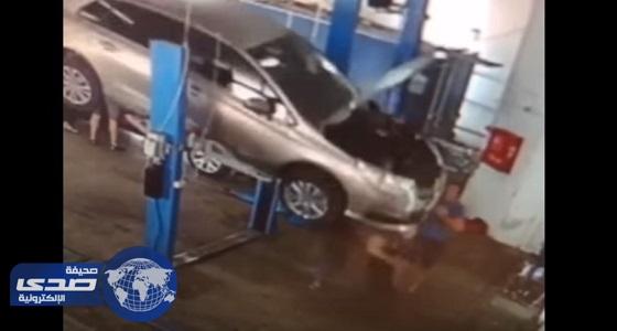 بالفيديو.. سيارة تسقط على عاملين في ورشة وتنهي حياتهما