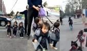 بالفيديو.. رجل يربط أحفاده الثلاثة بحبل أثناء عبوره الطريق