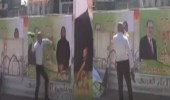 بالفيديو.. عراقي يضرب لافتات المالكي وعلاوي بالأحذية