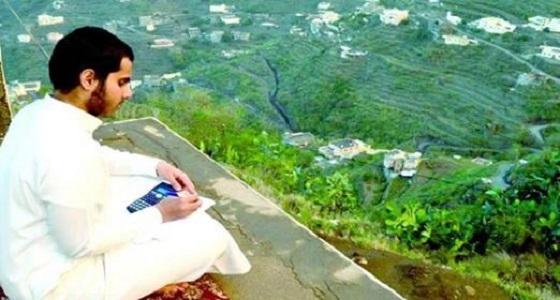 صورة ساحرة لطالب يذاكر دروسه أعلى قمم الجبال