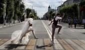 """متزوجان جدد يعبران الطريق خلال إقامة بطولة كأس العالم """" روسيا-2018 """" في مدينة سامارا"""