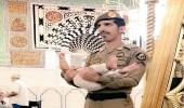 صورة تجسد الإنسانية.. عسكري يحمل طفلا ليتمكن والده من الصلاة بالمسجد النبوي