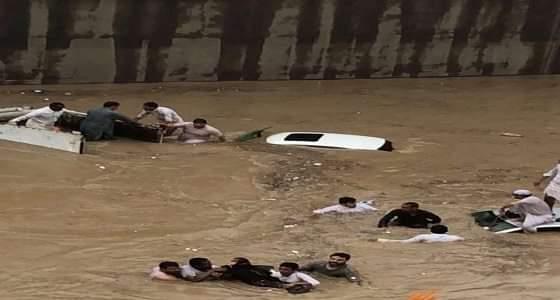 مواطنون يحاولون إنقاذ عائلة غرقت سيارتهم في نفق طريق ديراب