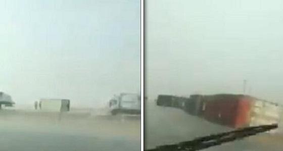 بالفيديو.. عاصفة قوية تتسبب في انقلاب عدة شاحنات بطريق الرياض - الدمام