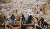 بالصور.. موظفو نيوم يعيدون بناء جسر جرفته الأمطار