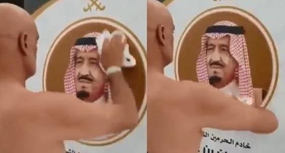 بالفيديو.. حاج يزيل آثار المطر عن صورة خادم الحرمين