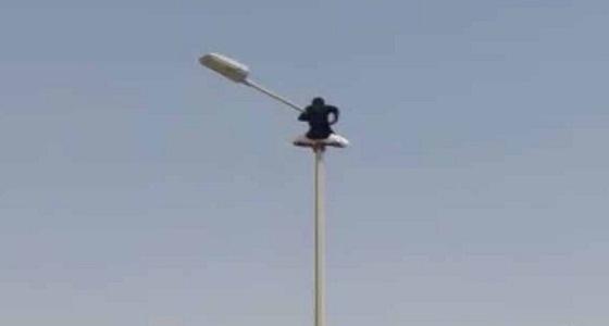 طالب يتسلق عمود إنارة بجوار مدرسته ثم يتأرجح