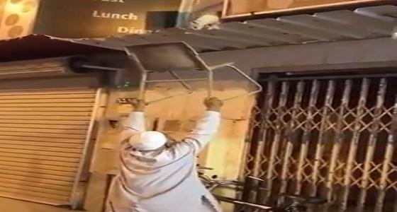 بالفيديو.. مسن يساعد قطة على النزول من سقف أحد المحلات