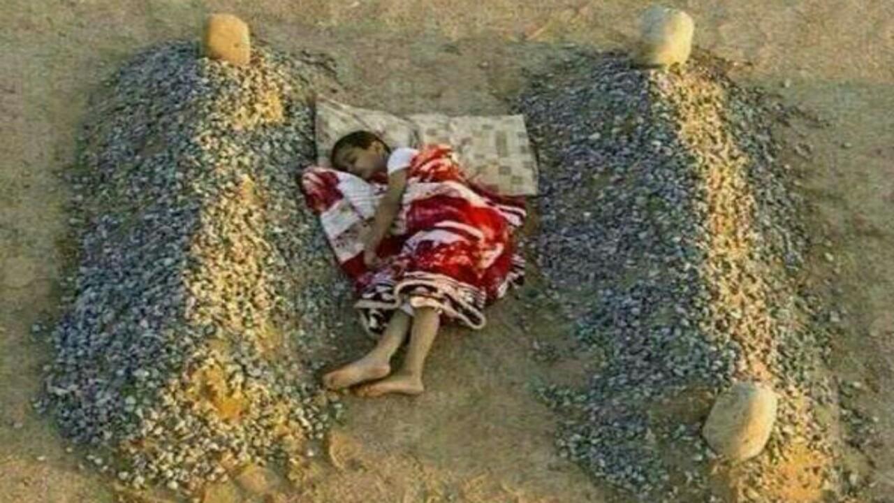 حقيقة صورة الطفل النائم بين قبري والديه