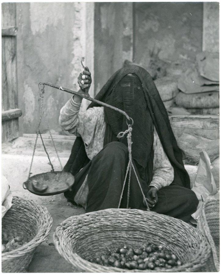 صورة نادرة لامرأة تزن التمور بسوق الظهران