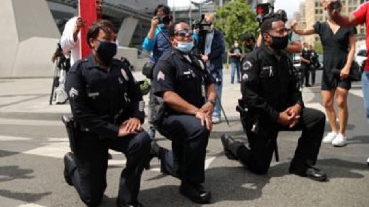 بالصور.. الشرطة الأمريكية تركع أمام المتظاهرين
