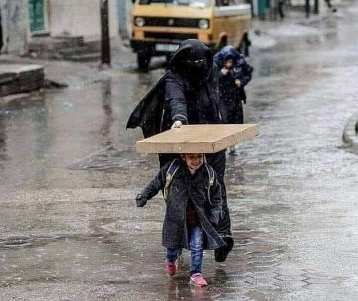 صورة جميلة لأم تحنو على طفلها تحت المطر