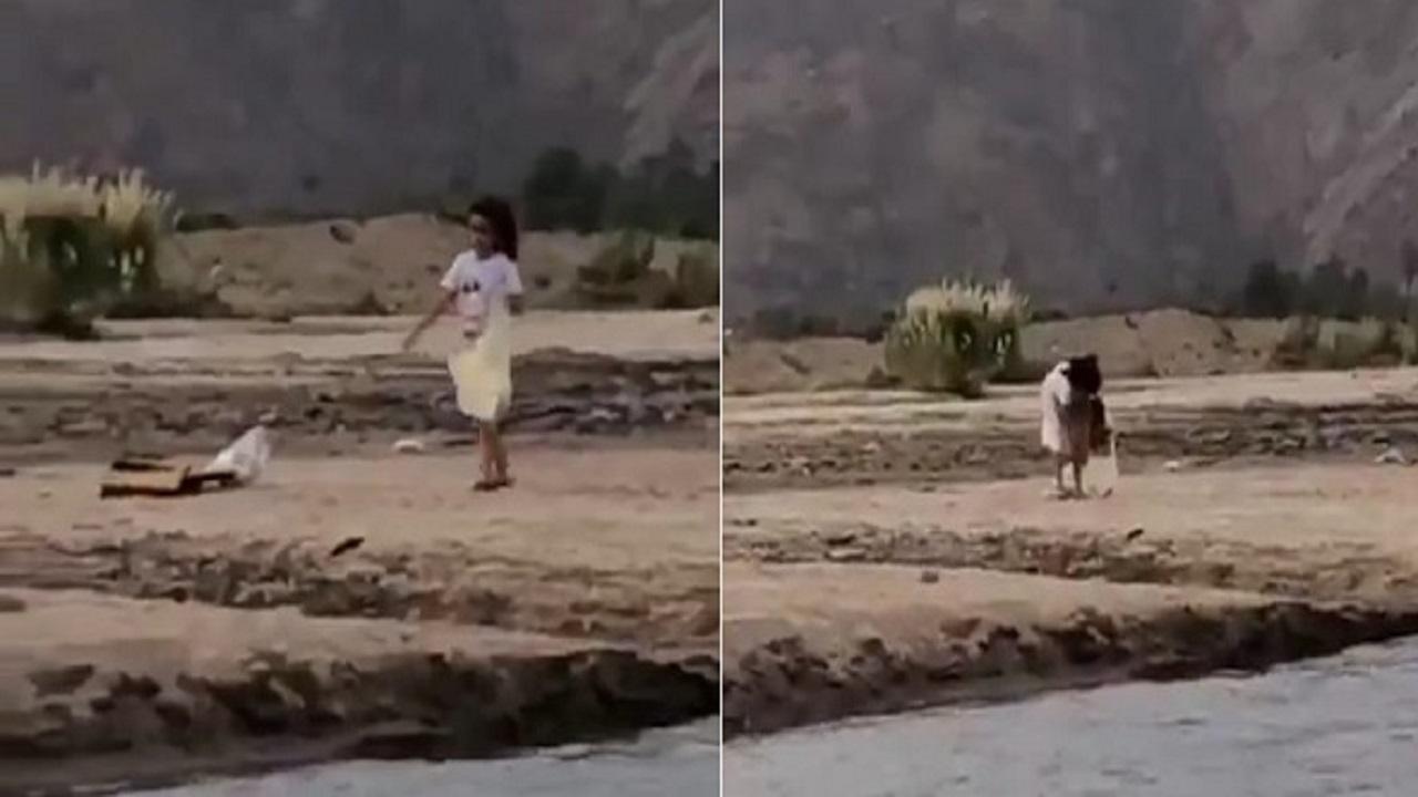 بالفيديو.. طفلة تعطي درساً للكبار وتنظف بقايا المتنزهين على ضقاف وادي نجران