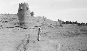 صورة لطفل يقف أمام الأسوار المحيطة بمحافظة مرات في الرياض