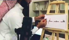 بالفيديو.. معلم يحول غرفة داخل منزله إلى فصل متكامل لشرح الدروس الافتراضية لأبنائه