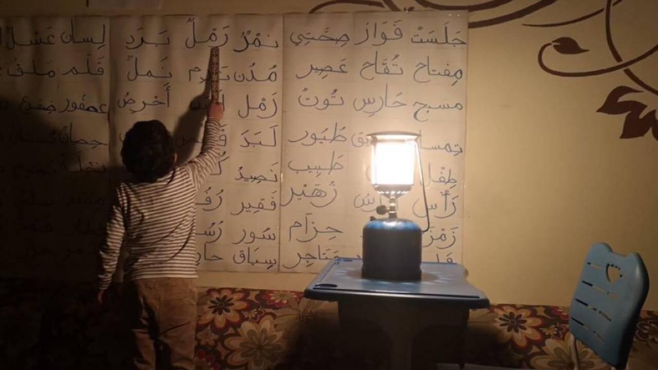 طالب يذاكر أثناء انقطاع الكهرباء متحديًا الظروف