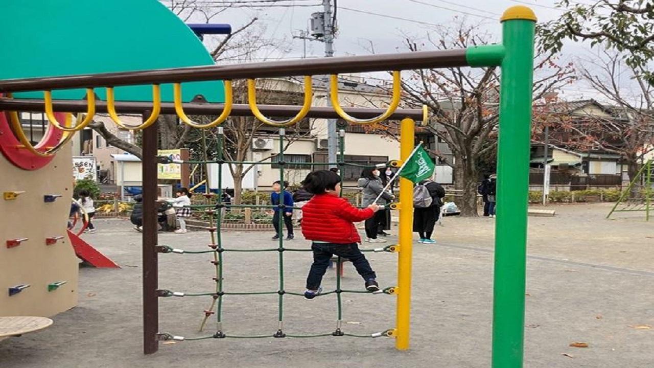 شاهد.. طفل ياباني يتعلق بالعلم السعودي ويحمله معه أينما ذهب