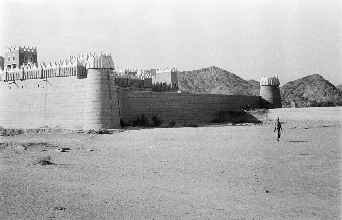 صورة قديمة لرجل يقف بجانب قصر إمارة نجران