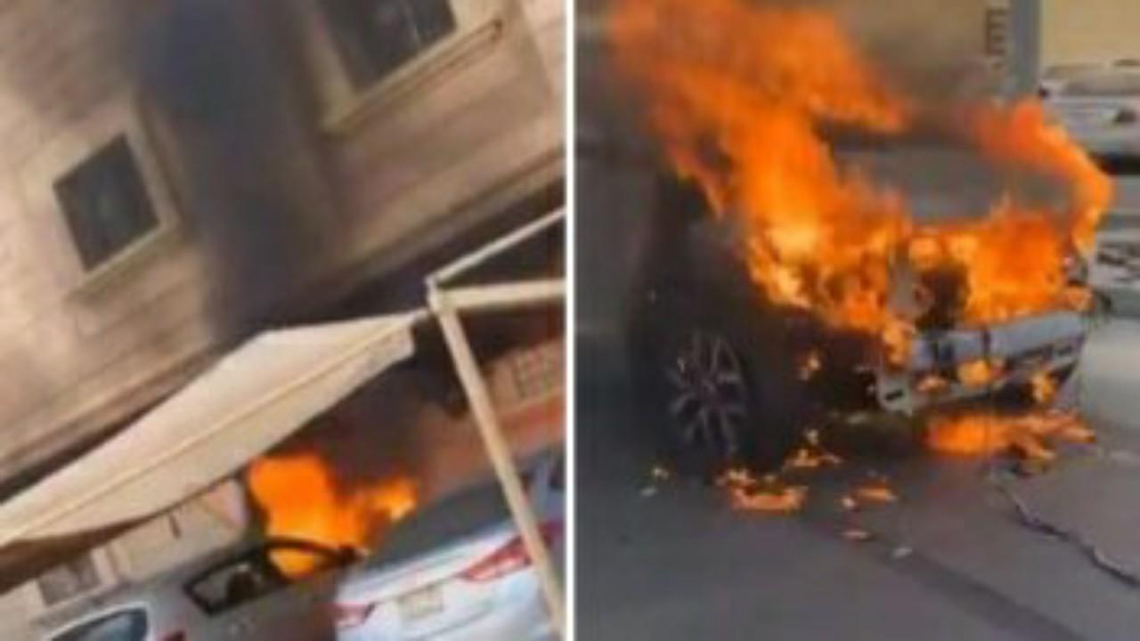 """مواطن يسحب سيارة مشتعلة بعد اندلاع حريق في مواقف السيارات أمام منزل بالدمام"""" فيديو """""""