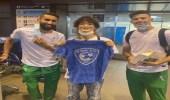 مشجع ياباني يحمل شعار الهلال أثناء استقباله الأخضر الأولمبي ويلتقط صورة مع الفرج والحمدان