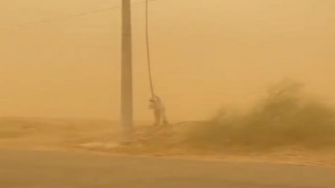 """منسوبو """"الكهرباء"""" يؤدون عملهم بأحد المواقع في جازان رغم العواصف الرملية """"فيديو"""""""