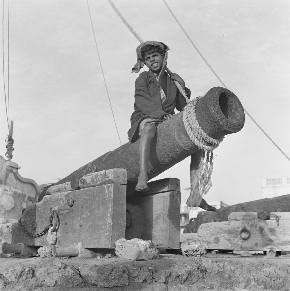 صورة رائعة لصبي يجلس فوق مدفع في ميناء الدمام