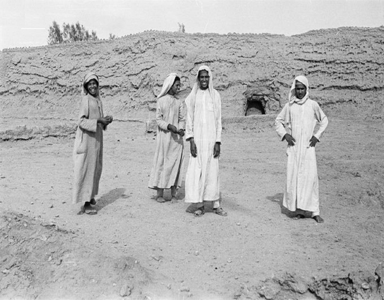 صورة لطفلين ورجلين يقفان أمام أسوار محافظة مرات قبل 76 عام
