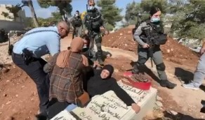 أم فلسطينية تنهار من البكاء وتتشبث بقبر ابنها أمام قوات الاحتلال