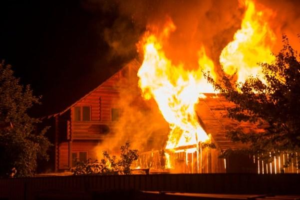 Casa de madera en llamas en la noche | Foto Premium