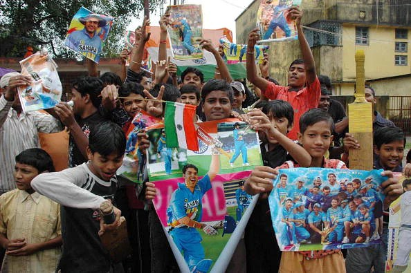 Indian cricket supporters hold posters a