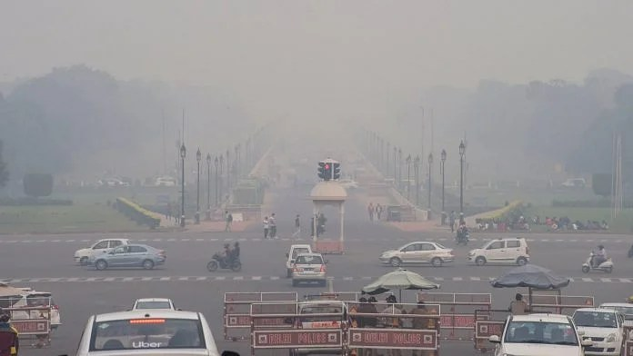 Vehicles ply on Rajpath shrouded in smog, in New Delhi