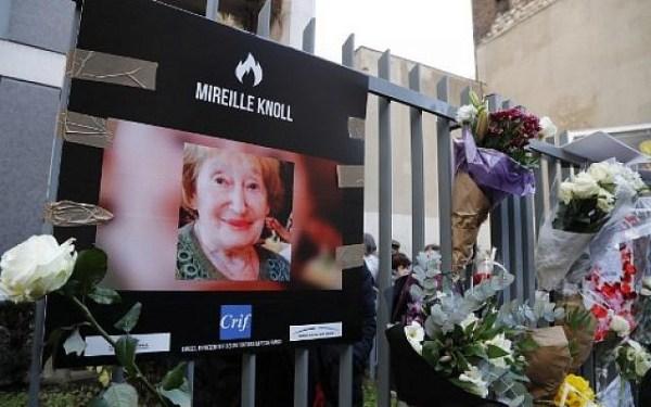 Une photo de Mireille Knoll et des fleurs sont placées sur la clôture entourant son immeuble à Paris, le 28 mars 2018 (Crédit : François Guillot / AFP)