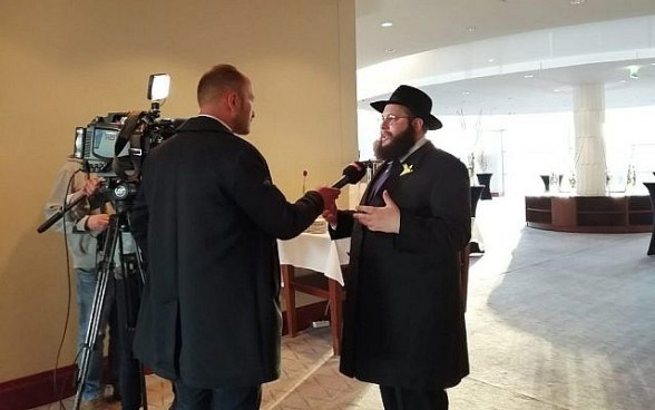 Rabbi Shalom Ber Stambler speaks to the Polish media ahead of sundown at the Warsaw Hilton, April 19, 2019. Hundreds gathered to celebrate the first seder in the former Warsaw Ghetto since it was razed in 1943. (Courtesy Chabad of Warsaw/via Times of Israel)