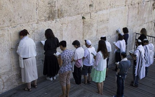 A group of people praying against the Wall, backs to the cameras.