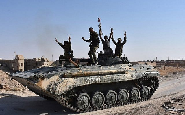 Syrian government forces celebrate in the eastern Syrian city of Deir Ezzor on September 11, 2017, as they continue to press forward with Russian air cover in the offensive against Islamic State terror group. (AFP Photo/George Ourfalian)