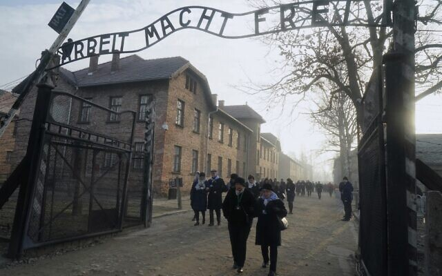 """Holocaust survivors walk below the gate with its inscription """"Work sets you free"""" after a wreath laying at the death wall at the memorial site of the former Nazi death camp Auschwitz during ceremonies to commemorate the 75th anniversary of the camp's liberation in Oswiecim, Poland, on January 27, 2020 (JANEK SKARZYNSKI / AFP)"""