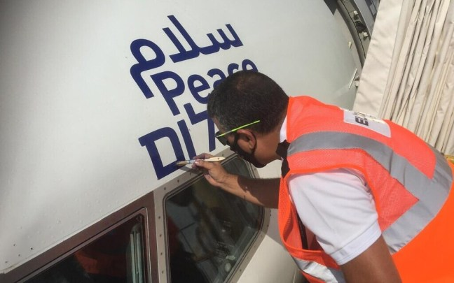 A peace logo in Arabic, English and Hebrew is painted on El Al flight 971 on August 30, 2020 ahead of its maiden direct flight from Tel Aviv to Abu Dhabi (El Al spokesperson)