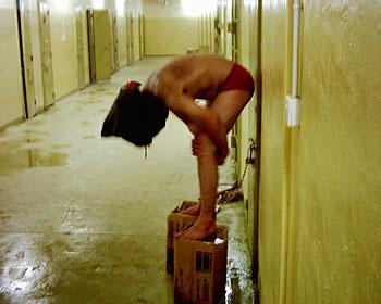 Bild aus Abu Ghraib eines Gefangenen auf einem Hocker mit Kapuze.