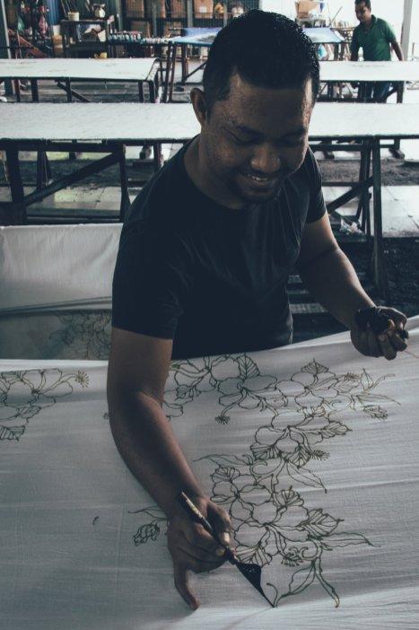 Craft Batik Artist, der die Wachsoutlines per Hand zeichnet