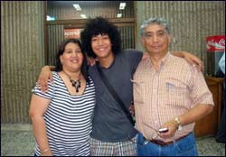 Carlos Villareal (midten) en av utvekslingsstudentene landet i sitt hjemland Colombia søndag. Her poserer han med sine foreldre, lykkelig over å være tilbake. Foto: AP