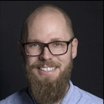 Bartosz Goralewicz, bearded and in glasses, smiling in passport photo