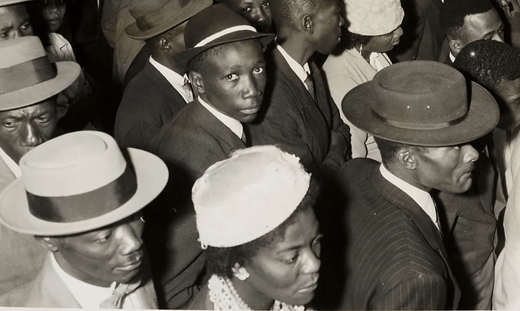 View of people of colour, with central young man looking up directly to camera.