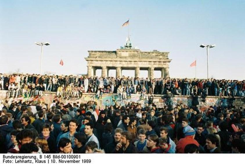 Tysiące ludzi przy Bramie Brandenburskiej stojących naiprzedMurem.
