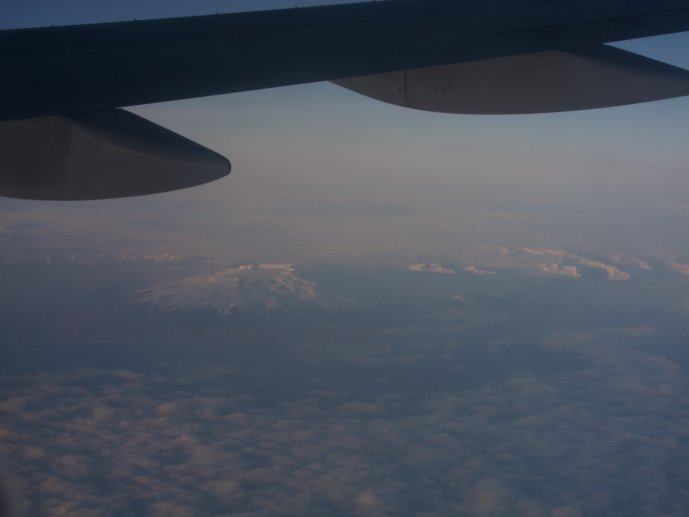 Photograph of snow covered mountains in Iceland through the window of a plane